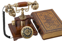 Ancient phone and book. Are photographed on the white background Stock Images