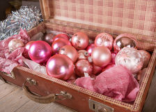 Ancient pink Christmas tree toys in antique suitcase. Ancient old pink Christmas tree toys in antique suitcase Royalty Free Stock Images