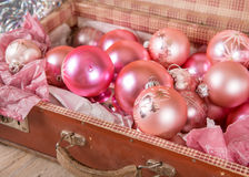 Ancient pink Christmas tree toys in antique suitcase. Ancient old pink Christmas tree toys in antique suitcase Royalty Free Stock Image