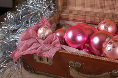 Ancient pink Christmas tree toys in antique suitcase. Ancient old pink Christmas tree toys in antique suitcase Stock Photos