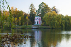 Ancient pink pavilion in autumn park. On a lake Stock Images
