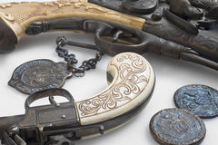 Ancient pistols and old coins. Stock Photo