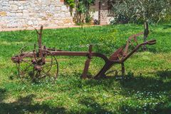 Ancient plow in rusty metal on a meadow stock photo