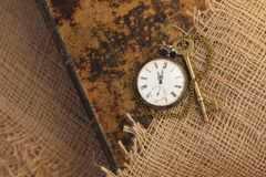 Ancient pocket watch and key on old folio half-covered with old sackcloth. Time passing concept. Knowledge eternity concept. Ancient pocket watch and key on old royalty free stock photo