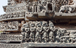 Ancient praying people on old wall of Hindu temple. Sculpured stone relief carvings from 12th century temple, Karnataka Stock Photo