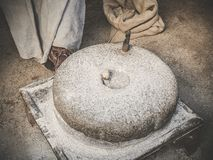 The ancient quern stone hand mill. Old grinding stones straw around Stock Image