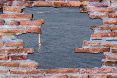 Ancient red brick wall over the blue sea. Stock Image
