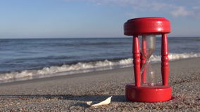 Ancient red broken hourglass sandglass clock on sea beach sand. Summer time concept stock footage