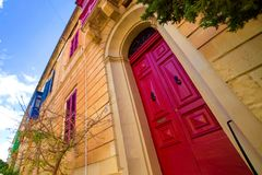 An ancient red door in a house with multicolored windows in Malta. A big ancient red door in a house with multicolored windows in Malta Stock Images
