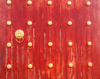 Ancient red wooden gate with lion door knocker Royalty Free Stock Photo