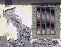 An ancient red wooden shuttered window in a frame with peeling faded green paint in an old house wall with broken cracked cement. Walls covering old stone royalty free stock photography