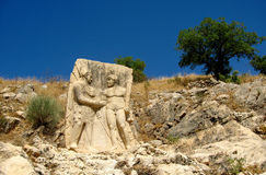 Ancient relief: Hercules shakes hands with King Antiochus. Turkey, Nemrut Dag National park Stock Image