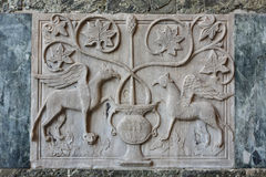 Ancient relief of two mythical grifffins. Byzantine relief of two griffins outside Saint Mark Basilica in Venice Royalty Free Stock Photo