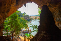An ancient religious cave. Inside view of the beautiful landscape with the boats. Hpa-An, Myanmar. Burma. Amazing view, religious carving on limestone rock in Stock Photo