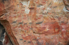 Ancient rock art on cave wall. Ancient indigenous rock art of Patagonia, Argentina, depicting a herd of guanaco (related to the llama), and human hands Stock Photo