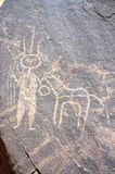 Ancient rock art in Niger of a figure and animal. Ancient rock art in Niger depicting one round headed figure and an animal royalty free stock photo