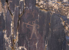 Ancient rock drawings, human with bow and arrow, hunting. Sarmish Gorge, Navoi Kermine, Uzbekistan Stock Photos