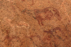 Ancient rock paintings African mountains ion a beige background Royalty Free Stock Image