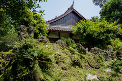 Ancient rockery before Chinese traditional building in sunny sum Royalty Free Stock Photos