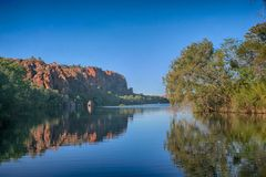 Ancient rocks reflected in calm water at Lake Argyll. Ancient rocks and leaning gums reflected in calm water Royalty Free Stock Photo