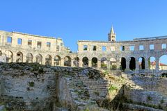 Ancient Roman Amphitheater and Church Bell Tower in Pula, Istria. Exterior wall and arches of the ancient Amphitheater and bell tower of the Church of Saint Royalty Free Stock Image