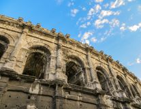 Top of Ancient Roman Amphitheater with Blue Sky. Ancient Roman amphitheatre in the south of France. Exterior view from street level of arches and cornice at the Royalty Free Stock Photography