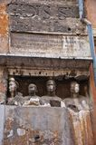 Ancient Roman Carvings. Ancient carvings in the walls in Rome showing 4 figures looking out into Rome with Latin inscription above Royalty Free Stock Photos