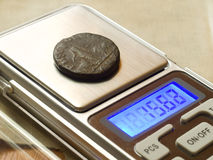 Ancient Roman coin. Ancient Roman bronze coin  on electronic scales Royalty Free Stock Image