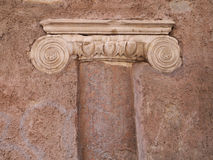 Ancient Roman Column build into wall,  Rome, Italy. Top of ancient Roman Column build into red wall,  Rome, Italy Royalty Free Stock Image