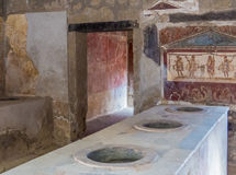 Ancient Roman kitchen in Pompeii. Kitchen of an ancient Roman house with frescoes in Pompeii, Campania, Italy Stock Image