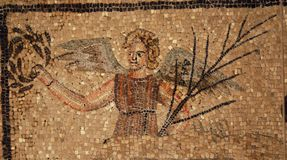 Ancient roman mosaic of an angel. Appearing to hold in one hand a branch and in the other a wreath in the patriarchal basilica of Aquilea.  This close-up  is a Stock Photo