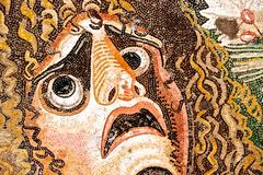 Ancient roman mosaic with fearful face. Detail of an ancient roman mosaic with a fearful face Stock Photo