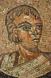 Ancient roman mosaic of rich patron. Roman mosaic of a sever looking man in the patriarchal basilica of Aquilea.  This close-up  is a segment of an immense Stock Photo