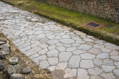Ancient Roman road. Narrow paved road is in the middle of the ancient Roman ruins. Pompeii has been a popular tourist destination for over 250 years Royalty Free Stock Photo