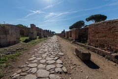 Ancient Roman road paved with stones for carriage. Decumano maxi. Mum in Ostia ancient 2nd century. Sun, sea pines and Roman ruins in the background stock images
