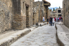 Ancient Roman Street. Visitors on an ancient Roman street in the ruined city of Pompeii Stock Image