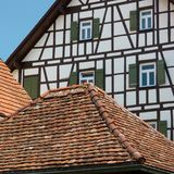 Ancient roof tiles in front of truss façade. Very well maintained medieval houses, medieval architecture, medieval style, Window with folding shutters in royalty free stock photo