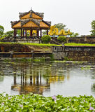 Ancient Rotunda Reflected in Pond. An ancient Vietnamese rotunda reflects in the pond with a giant dragon sculpture in the distance Stock Photos