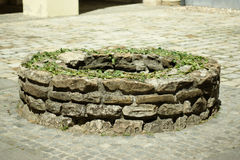 Ancient round stone brick well, little decorated. Now just a wishing well Stock Images