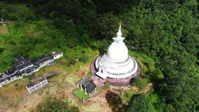 Aerial close-up shot from the temple in mountains of Adam Peak in Sri Lanka. Ancient round temple in the middle of the valley of mountains of Adam Peak in Sri stock footage