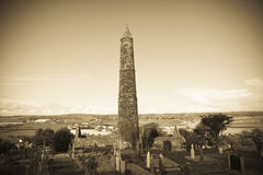 Ancient round tower and celtic graveyard with cathedral Stock Images