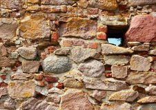 Ancient ruin wall of rocks with hole Stock Images