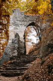 Ancient ruined arch in the wall of the castle on the hill. In the autumn forest on a cloudy day Royalty Free Stock Photos