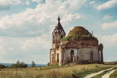 Ancient ruined Russian church or temple overgrown with grass among field. Toned Royalty Free Stock Image