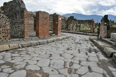 Ancient ruins in Pompeii. An antique roman stone street through ruins of Pompeii,Italy Royalty Free Stock Images