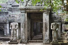 Ancient ruins of Preah Khan temple with stone carving, Siem Reap, Cambodia. Two male statues protecting temple entrance. Ancient sacred place. Cambodian Royalty Free Stock Image
