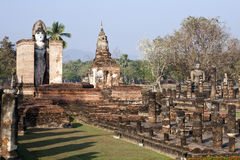 Ancient Ruins of Siam in Sukothai. A tall Buddha statue stands watch over the dilapidated ruins at Sukothai Historical Park in northern Thailand stock photos