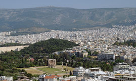 Ancient ruins surrounded by modern Athens. Overview of Athens, Greece with ancient ruins in foreground and a backdrop of the modern city Stock Image