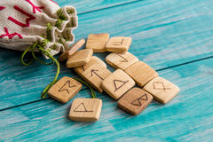 Ancient runes, canvas bag with embroidery on old vintage wooden background. Selective focus. Royalty Free Stock Image
