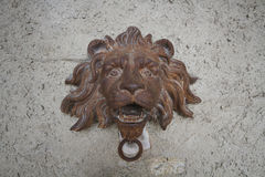 Ancient rustic steel iron crafting of lion head statue  with Wall brick stone sculpture, old historical door bell Royalty Free Stock Photos